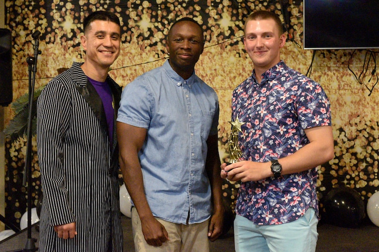 U.S. Air Force Col. Ricky Mills, 17th Training Wing commander and Chief Master Sgt. Lavor Kirkpatrick, 17th TRW command chief, present U.S. Army Pfc. Chris Frazier, 344th Military Intelligence Battalion student, an award for the semi-annual Goodfellow's Got Talent show at the Crossroads Student Ministry Center on Goodfellow Air Force Base, Texas, July 13, 2018. Frazier won second place for his performance. (U.S. Air Force photo by Senior Airman Randall Moose/Released)
