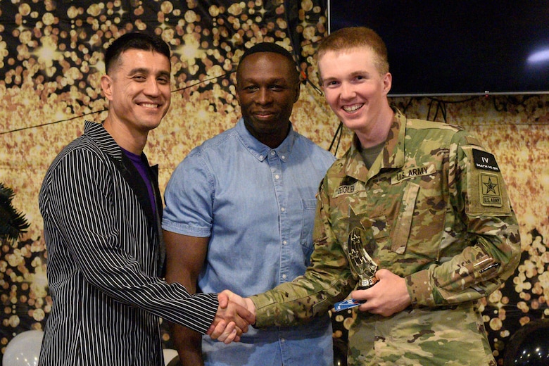 U.S. Air Force Col. Ricky Mills, 17th Training Wing commander and Chief Master Sgt. Lavor Kirkpatrick, 17th TRW command chief, present U.S. Army Pvt. John Zeigler's, 344th Military Intelligence Battalion student, an award for the semi-annual Goodfellow's Got Talent show at the Crossroads Student Ministry Center on Goodfellow Air Force Base, Texas, July 13, 2018. Zeigler won first place for his performance. (U.S. Air Force photo by Senior Airman Randall Moose/Released)