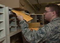 "Airman 1st Class Brandon Beard, 60th Force Support Squadron, sorts inter-office mail, better known as ""holey joe"" envelopes, May 5, 2018, Travis Air Force Base, Calif. The 60 FSS Official Mail Center is responsible for processing mail for Travis AFB, David Grant USAF Medical Center, and commercial company deliveries. (U.S. Air Force Photo by Heide Couch)"