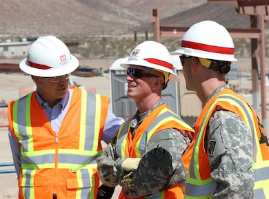 Col. Kirk Gibbs, U.S. Army Corps of Engineers Los Angeles District commander, center, speaks with other Corps employees while touring several project sites during a Sept. 9 to 10, 2015, visit to the National Training Center at Fort Irwin, California.