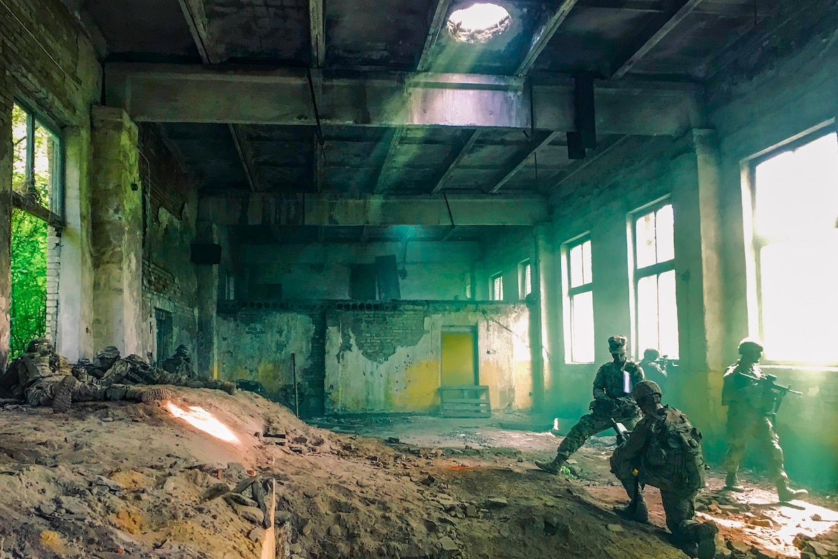 Soldiers stand in a room filled with dirt and green haze.