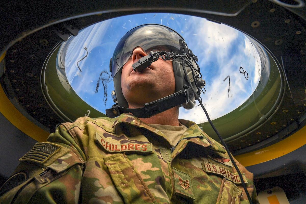 An airman looks at the sky through a window.