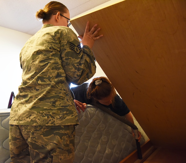 Staff Sgt. Hailey Staker, an Airman dorm leader, lifts a bed frame so Airman 1st Class Casi Smith, a 28th Security Forces response force leader, can clean under it at Ellsworth Air Force Base, S.D., July 17, 2018. Airmen are responsible for cleaning their rooms before they out-process and move to a new home. (U.S. Air Force photo by Airman 1st Class Thomas Karol)