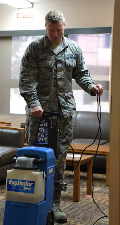 Staff Sgt. Jason Goss, an Airman dorm leader, uses a rug cleaner at Ellsworth Air Force Base, S.D., July 16, 2018. Dorm leaders ensure all six base dorms are maintained and kept in working order. (U.S. Air Force photo by Airman 1st Class Thomas Karol)