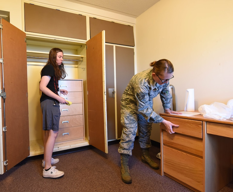 Staff Sgt. Hailey Staker, an Airman dorm leader, inspects the room of Airman 1st Class Riley Thomas, an electronic warfare journeyman, at Ellsworth Air Force Base, S.D., July 17, 2018. Staker and her colleagues are responsible for ensuring dorm airmen are processed in and out of the dorms efficiently. (U.S. Air Force photo by Airman 1st Class Thomas Karol)