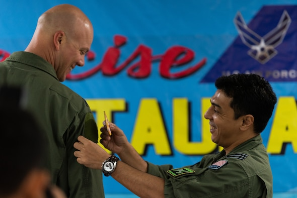 Royal Malaysian air force (RMAF) Lt. Col. Syed Faisal, RMAF exercise director, places a patch on U.S. Air Force Lt. Col. Barry King II, U.S. Air Force exercise director, during the Cope Taufan 18 opening ceremony at Subang Air Base, Malaysia, July 13, 2018.