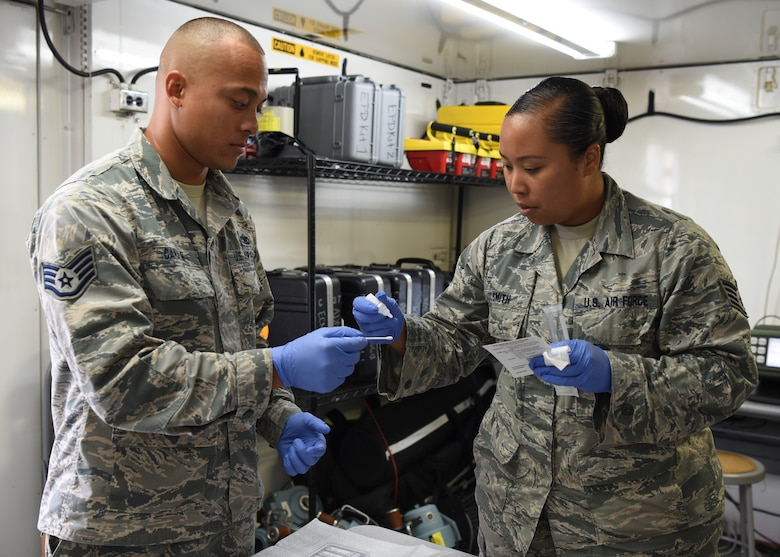 Staff Sgt. Michelle Smith, 51st Aerospace Medical Squadron NCO in charge of readiness plans and operations, demonstrates how to use a sampling kit to test for biological agents with Staff Sgt. Nikita Canalin, 51st Aircraft Maintenance Squadron avionics system technician, at Osan Air Base, Republic of Korea, July 9, 2018. During the Airman exchange, Canalin not only learned about day-to-day operations performed by medical technicians but also learned how to perform mission critical duties in a contingency. (U.S. Air Force photo by Airman 1st Class Ilyana A. Escalona)