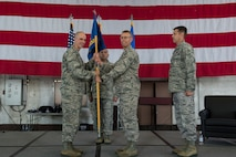 U.S. Air Force Col. Jason E. Bailey, 52nd Fighter Wing commander, left, passes the ceremonial guidon to Col. Greg Buckner, incoming 52nd Munitions Maintenance Group commander, right, during the 52 MMG change of command ceremony in Hangar 1 on Spangdahlem Air Base, Germany, July 17, 2018. (U.S. Air Force photo by Senior Airman Dawn M. Weber)
