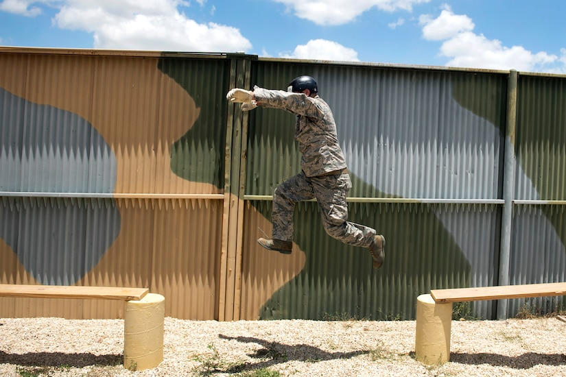 An airman leaps over a gap between planks during a leadership obstacle course.