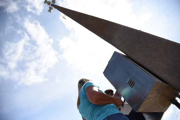 Skip Thomas, communication contractor, and Sharon Macy, 47th Communications Squadron installation Radio Frequency transmission systems manager, work on one of 16 poles connected to the giant voice system at Laughlin Air Force Base, Texas, on June 29, 2018. Laughlin's system, which comprises of 16 35-foot concrete poles, with four speakers individually pushing 400 watts of audio each, notifies base personnel of emergency situations, as well as marks the official start and finish of a duty day.  (U.S. Air Force photo by 1st Lt. Mickel McGann)