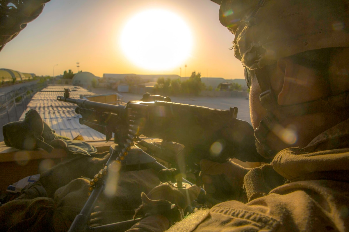 A Marine holds a weapon with the sun in the background.