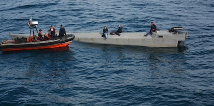 A Coast Guard Cutter Alert boarding team prepares to remove contraband from a suspected low-profile go-fast vessel in international waters