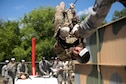 An airman navigates along a rope while upside-down during an obstacle course.