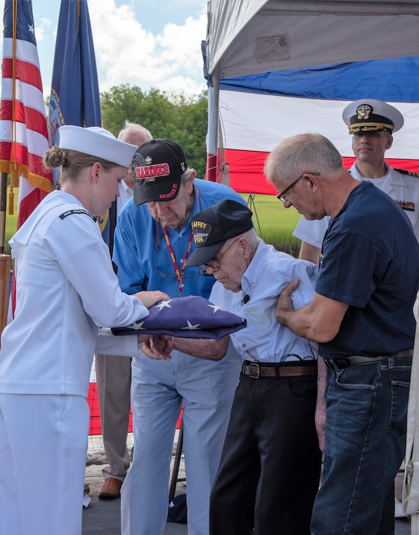 U.S. Navy Seaman Jacey Pruitt, left, a hospital corpsman serving at Naval Health Clinic Charleston, presents the American flag to WWII Veteran Waitman Kapaldo during a memorial service July 6, 2018, aboard the USS Laffey in Mount Pleasant, S.C.