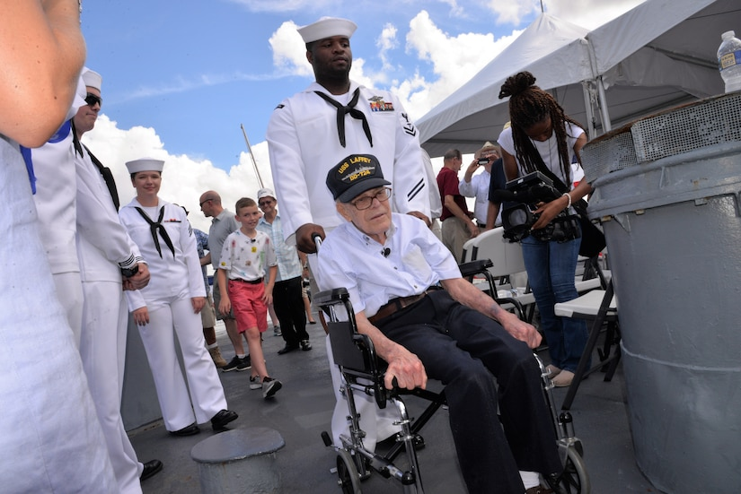 Petty Officer 2nd Class Clinton Leonard, a hospital corpsman serving at Naval Health Clinic Charleston, ushers WWII Veteran Waitman Kapaldo across the deck of the USS Laffey  July 6, 2018, at Patriots Point in Mount Pleasant, S.C.