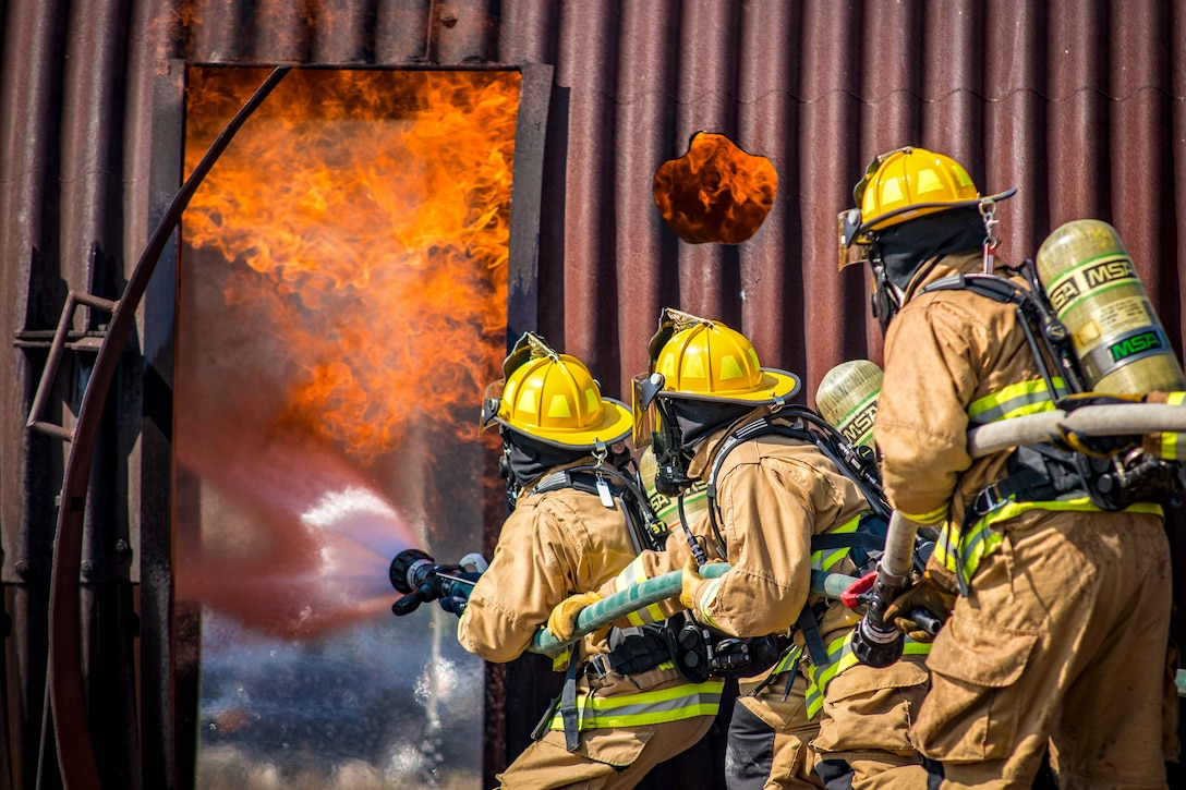 Three firefighters hold spray a fire with a firehose.