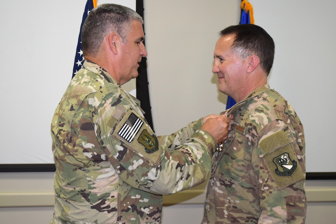 Col. James Phillips, former 919th Special Operations Wing commander, pins the Legion of Merit medal on Col. Brian Stahl following his retirement from the Air Force July, 15, 2018.