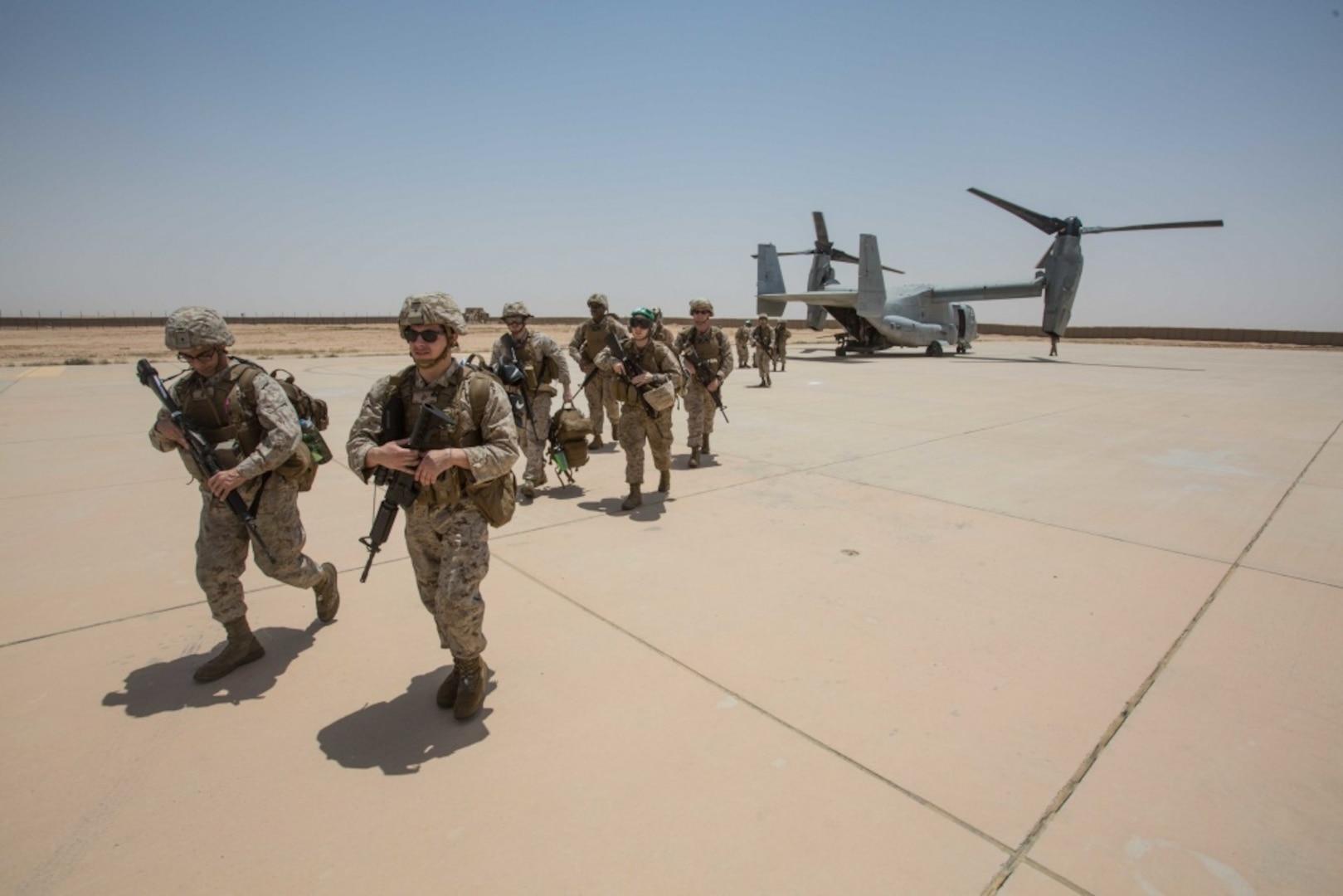 Marines walk from an MV-22B Osprey