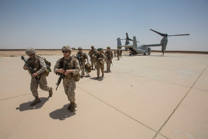Marines walk from an MV-22B Osprey