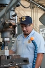 Carlos Casasola, 12th Maintenance Group metals technology shop, machinist, forms a flat surface on a block of metal using a vertical milling machine, July 2, 2018, at Joint Base San Antonio-Randolph, Texas. The maintenance group executes more than 40,000 flight hours annually supporting six training operations squadrons.