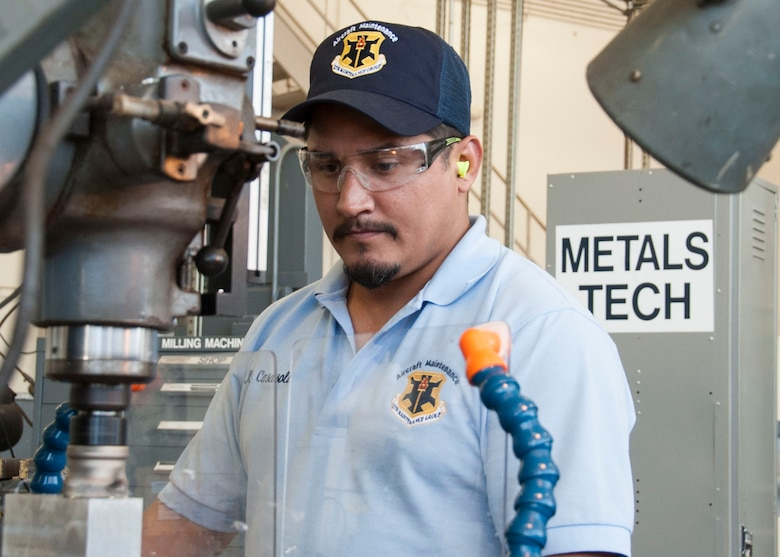Carlos Casasola, 12th Maintenance Group metals technology shop, machinist, forms a flat surface on a block of metal using a vertical milling machine, July 2, 2018, at Joint Base San Antonio-Randolph, Texas. The maintenance group executes more than 40,000 flight hours annually supporting six training operations squadrons. (U.S. Air Force photo by Tech. Sgt. Ave I. Young)