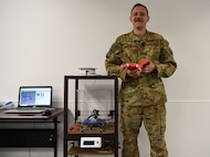 Tech Sgt. Zachary Zilm, 582nd Operation Support Squadron NCO in charge of group training, shows off his first, fully functional, 3D prosthetic hand July 3, 2018, on F.E. Warren Air Force Base, Wyo. Zilm received approval to begin making the prosthetics during the 4th of July holiday. Zilm's goal now is to put together a team to make the creation process smoother, which would allow more hands to be made.