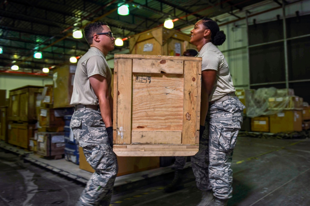 Two airmen carry a box.