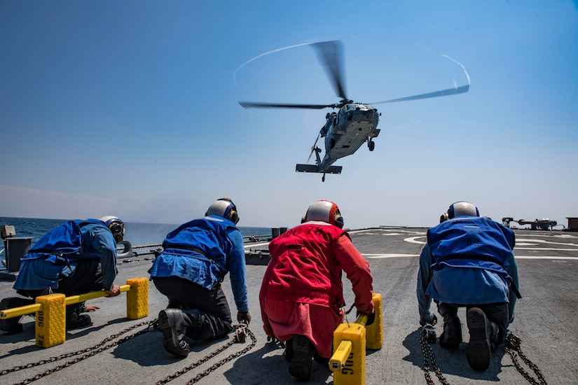 A helicopter prepares to land on the flight deck of a ship.