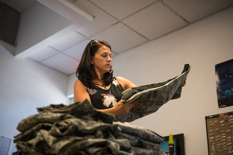 Melanie Patrick, volunteer at the Airman's Attic, checks a pair of Airman Battle Uniform pants for damages at the Airman's Attic on Cannon Air Force Base, N.M., July 10, 2018. The Airman's Attic receives most donations from people leaving their duty station. (U.S. Air Force photo by Airman 1st Class Vernon R. Walter III/Released)
