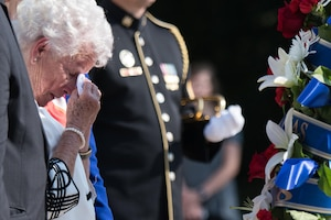 Woman helps soldier lay a wreath at the Tomb of the Unknown Soldier.
