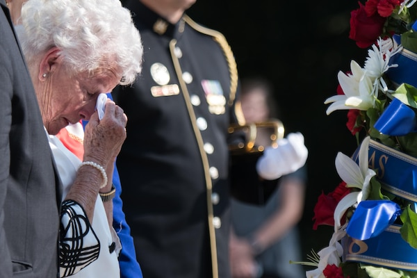 A woman reacts after laying a wreath down during a ceremony.