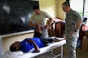 U.S. Air Force Maj. Brian Smith, a physical therapist with the 35th Medical Group, Misawa Air Base, Japan, center, and Tech. Sgt. Manuel Carrillo, a physical therapy technician with the 354th Medical Group, Eielson Air Force Base, Alaska, check a patient's range of motion at Tata Primary and Secondary School during Pacific Angel 18-3 in Luganville, Espiritu Santo Island, Vanuatu, July 16, 2018.