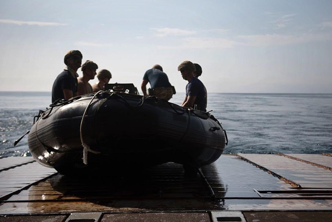 Sailors prepare to launch a combat rubber raiding craft.