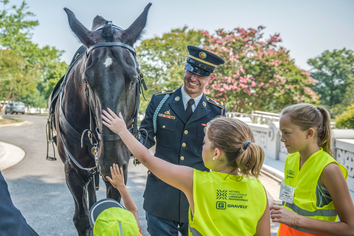 Children pet a horse as a soldier holds the reins.