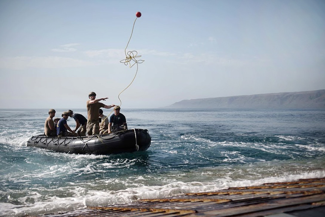 A sailor throws a retrieving rope from a combat rubber raiding craft.