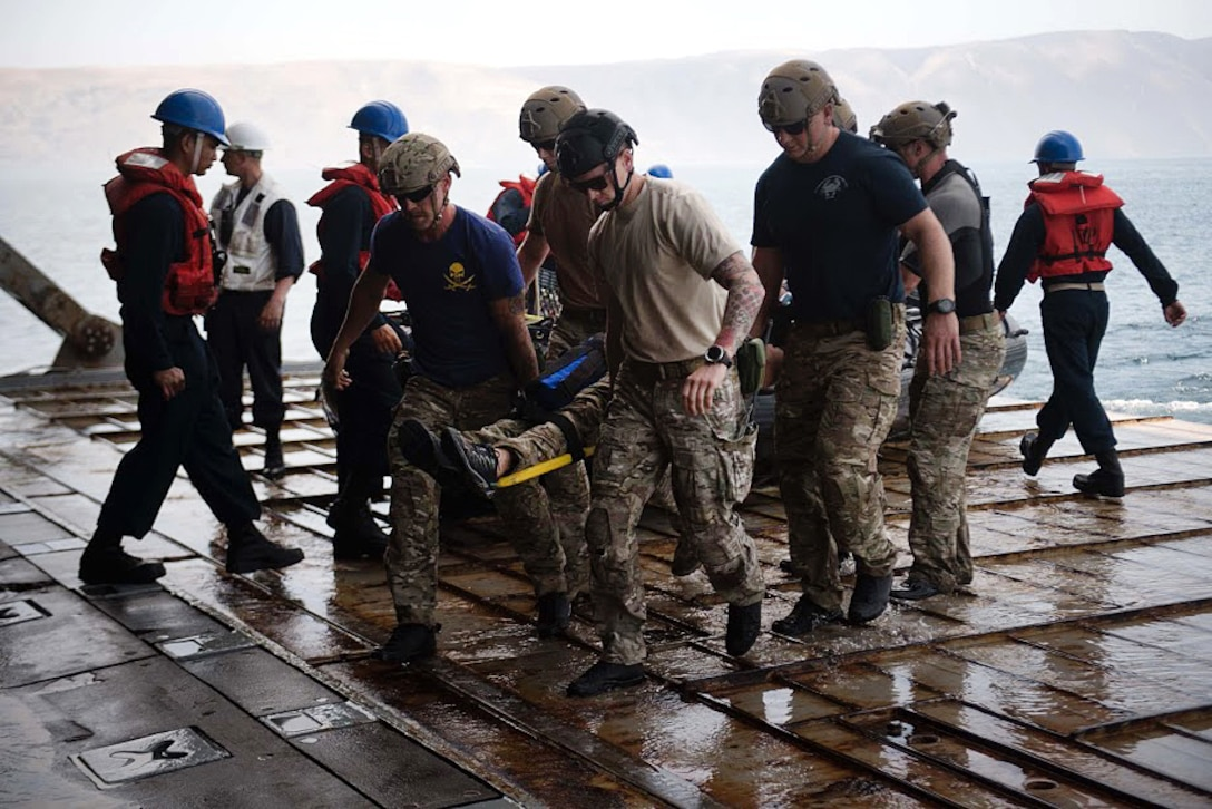 Sailors carry a mock casualty in a stretcher during a man-down drill.