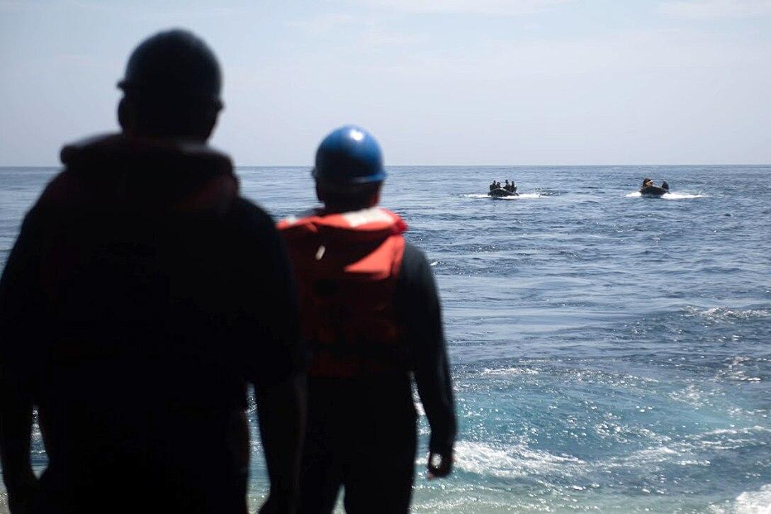 Sailors maneuver their combat rubber raiding crafts.