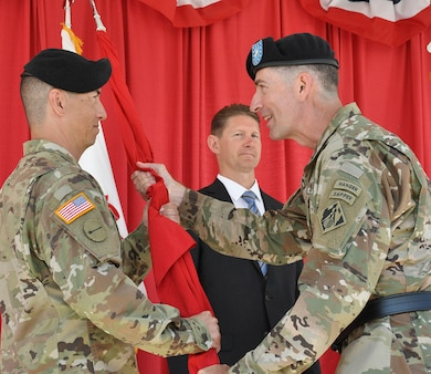 Brig. Gen. Pete Helmlinger, U.S. Army Corps of Engineers South Pacific Division commander, right, passes the flag to Col. Aaron Barta, incoming U.S. Army Corps of Engineers Los Angeles District commander, left, during a July 19 change of command ceremony at Fort MacArthur in San Pedro, California. The passing of the flag in military tradition represents the transfer of command.