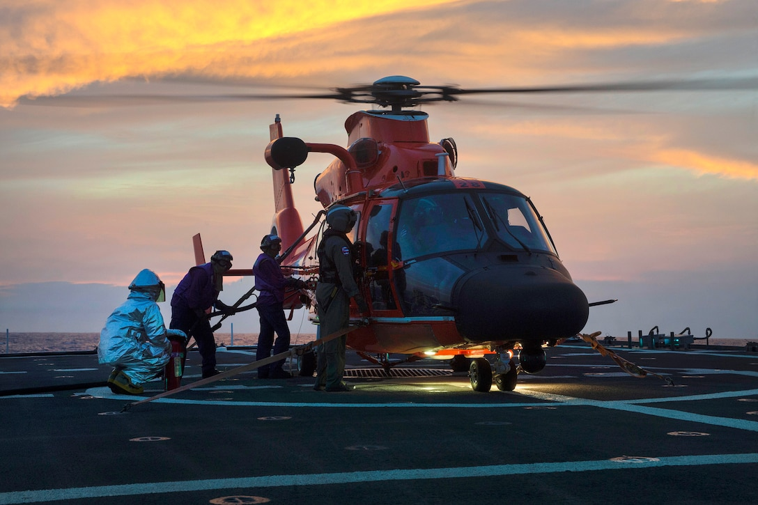 Coast Guard cutter crew refuels a helicopter.