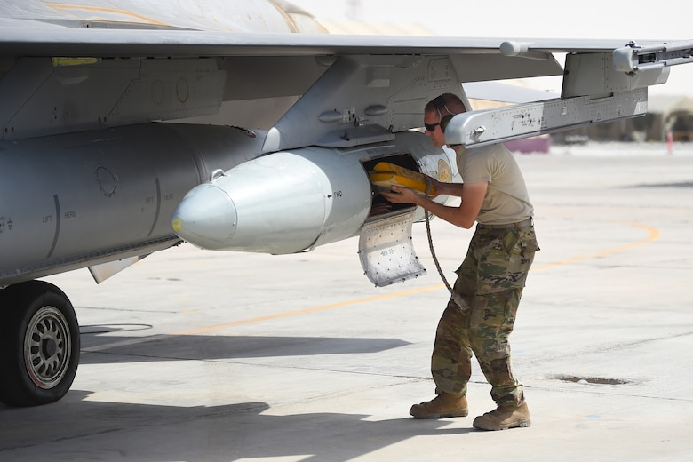 An Airman puts wood blocks into a travel pod of an F-16 fighter jet