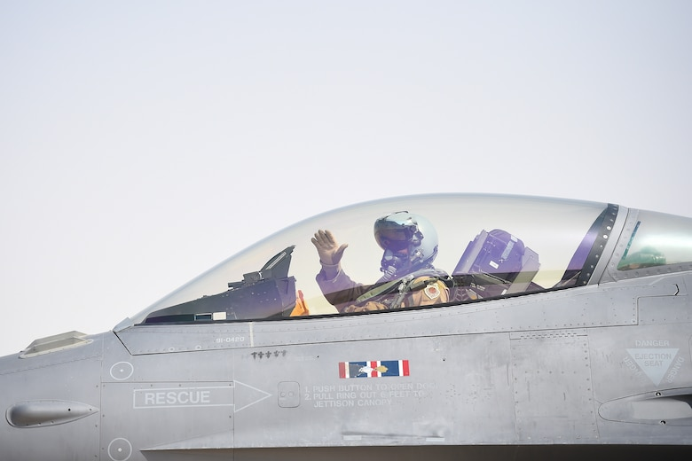 A pilot waves goodbye from inside the cockpit of an F-16