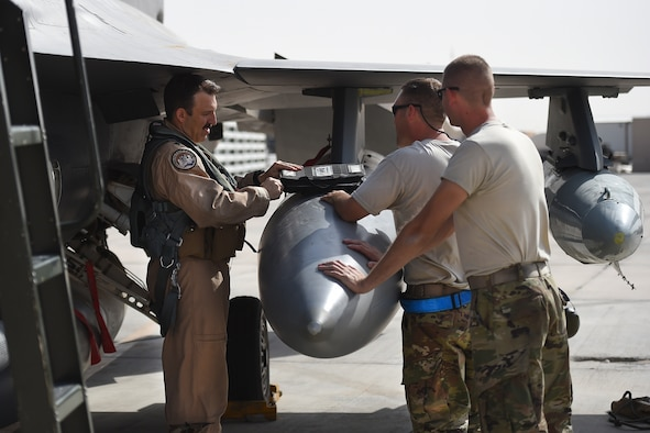Airman talk with a pilot in front of an F-16 fighter jet