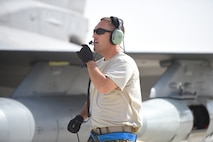 An Airman uses a head set to speaks in front of an F-16 fighter jet