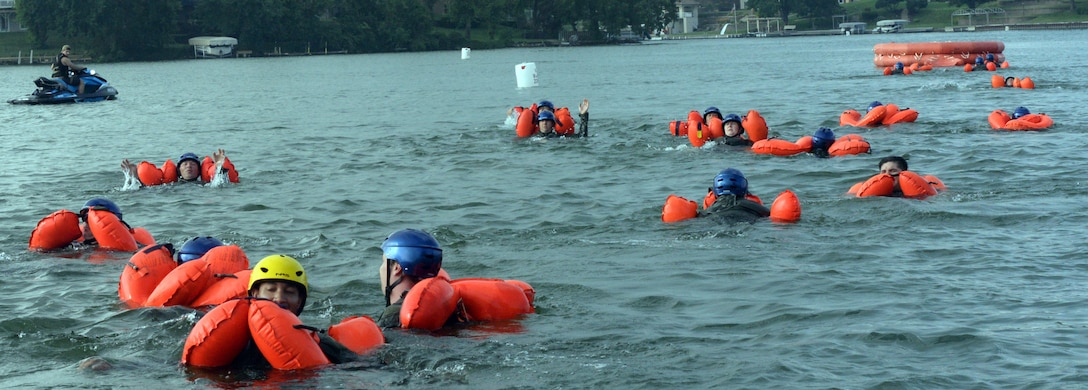 170th Group members, assigned to Offutt Air Force Base, Nebraska, swim toward a raft while participating in water survival and rescue training July 14, 2018. The aircrew members were briefed on the availability and use of tools contained in their survival gear before putting academics and theory to the test in the waters of a local lake.