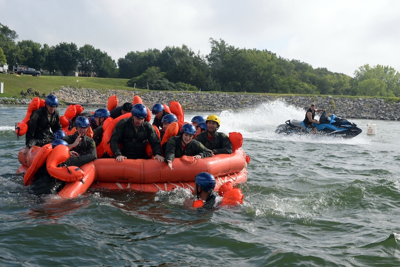 170th Group Citizen Airmen, assigned to Offutt Air Force Base, Nebraska, prepare their raft for rough seas, simulated by Staff Sgt. Kevin Battista, 55th Operational Support Squadron Survival Evasion Resistance Escape specialist, while participating in water survival and rescue training July 14, 2018. The aircrew members were briefed on the availability and use of tools contained in their survival gear before putting academics and theory to the test in the waters of a local lake.