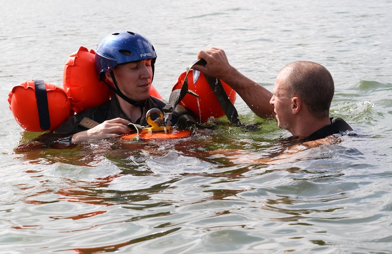 Maj. Kevin Selin, member of the 170th Group assigned to Offutt Air Force Base, Nebraska, is instructed in the use of an extraction tool by Staff Sgt. Neal Troyer, 55th Operational Support Squadron Squadron Survival Evasion Resistance Escape specialist, while participating in water survival and rescue training July 14, 2018. The hands-on water instruction included donning cold-water exposure suits; inflating and swimming with inflatable life preservers; and boarding and utilizing a 20-person survival raft.