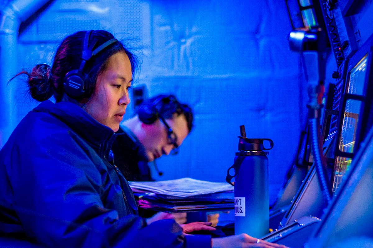 Two sailors work at screens in a blue room.