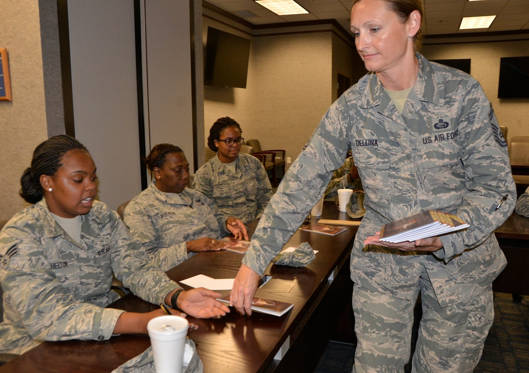 """Senior Master Sgt. Tricia DeLuna, Manager, Military Personnel Division, 1st Air Force (Air Forces Northern) and """"Four Lenses 4-Terperament Discovery"""" course facilitator, distributes course guides to the class July 12. The course is a personality assessment tool that helps participants enhance both their own self-awareness and their interpersonal communication skills. (Air Force photo by Mary McHale)"""