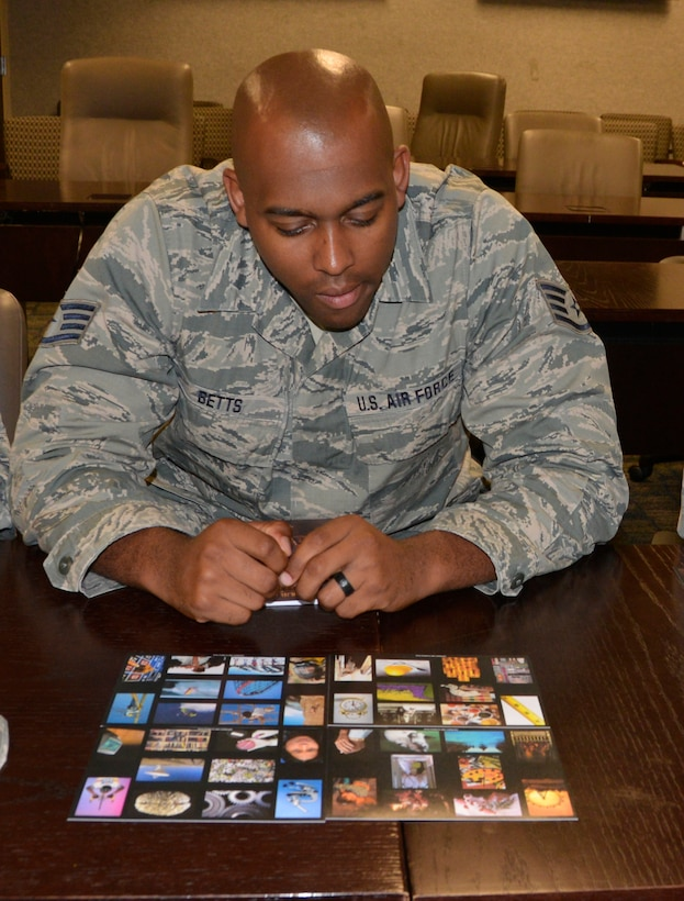 "Staff Sgt. Matthew Betts, personnel journeyman, 186th Air Operations Group, Meridian, Miss., looks over the course cards July 12 during the ""Four Lenses 4-Terperament Discovery"" course. The course is a personality assessment tool that helps participants enhance both their own self-awareness and their interpersonal communication skills. (Air Force photo by Mary McHale)"