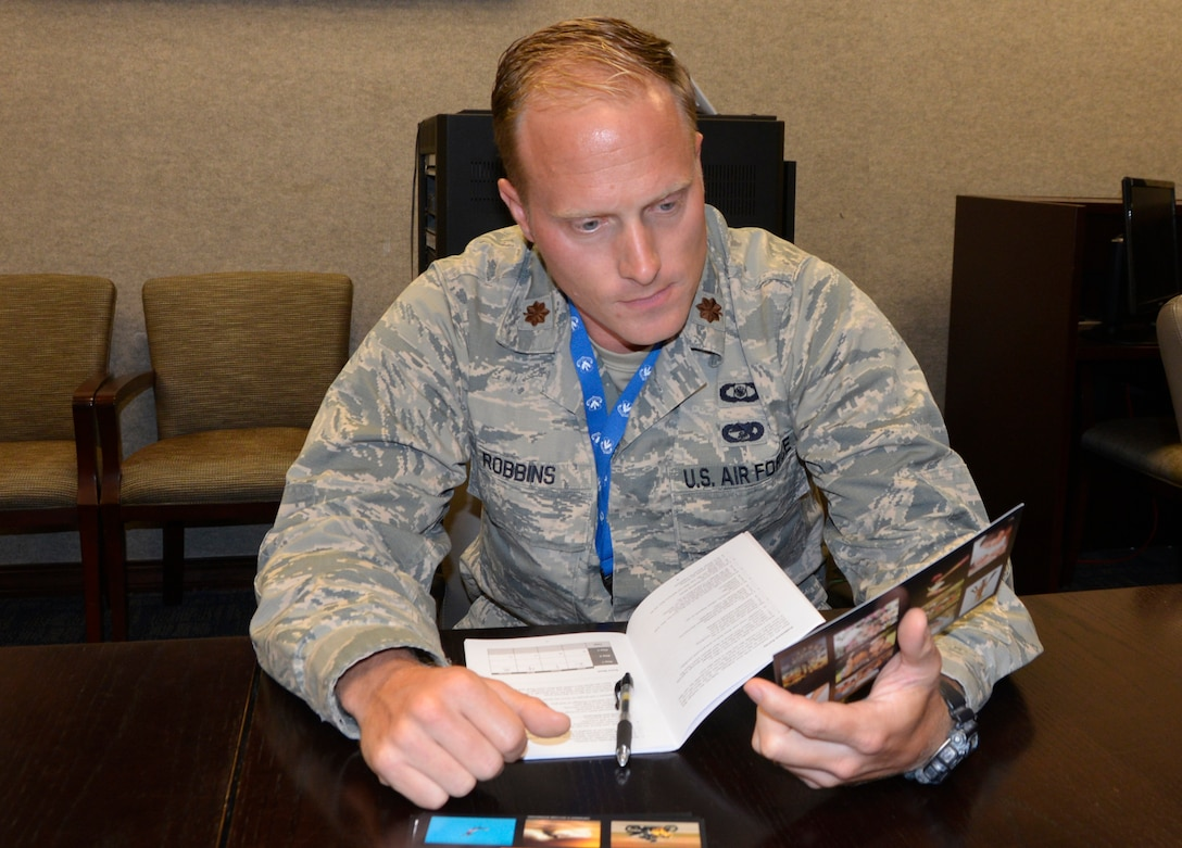 """Maj. Casey Robbins, executive officer to the 1st Air Force (Air Forces Northern) vice commander, looks over one of the course cards July 12 during the """"Four Lenses 4-Temperament Discovery"""" course. The course is a personality assessment tool that helps participants enhance both their own self-awareness and their interpersonal communication skills. (Air Force photo by Mary McHale)"""